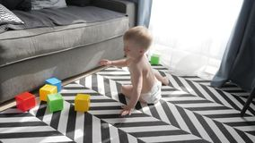 Λίγο αγοράκι που παίζει με τους ζωηρόχρωμους μικρούς φραγμούς ενός κατασκευαστή στο δωμάτιο στο πάτωμα Παιχνίδι παιδιών με χρωματ απόθεμα βίντεο