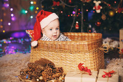 Λίγο αγοράκι στη συνεδρίαση καπέλων Santa σε ένα ψάθινο καλάθι Στοκ Φωτογραφίες