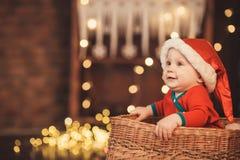 Λίγο αγοράκι στη συνεδρίαση καπέλων Santa σε ένα ψάθινο καλάθι Στοκ Εικόνα
