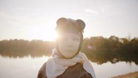 Λίγο αγόρι αεροπόρων στο αναδρομικό πειραματικό κοστούμι με το μαντίλι και γυαλιά που εξετάζουν τη κάμερα που χαμογελά στη λίμνη  απόθεμα βίντεο