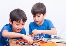 Λίγο αγόρι αμφιθαλών που παίζει την πλαστική εκπαίδευση σπιτιών φραγμών εσωτερική Στοκ Εικόνα