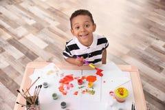 Λίγο αγόρι αφροαμερικάνων που χρωματίζει στον πίνακα Στοκ Εικόνα