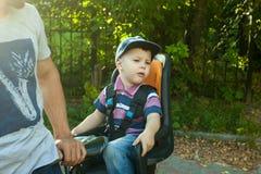 Λίγο αγόρι μικρών παιδιών σε ένα καπέλο του μπέιζμπολ στην ανακύκλωση καθισμάτων ποδηλάτων με τον πατέρα στη φύση στοκ φωτογραφία
