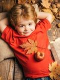 Λίγο αγόρι παιδιών βρίσκεται θερμά γενικά όνειρα του θερμού φθινοπώρου Το ξανθό αγόρι που στηρίζεται με ένα μήλο στο στομάχι βρίσ στοκ φωτογραφία