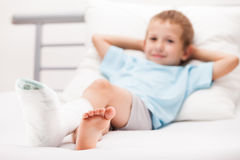 Λίγο αγόρι παιδιών με τον επίδεσμο ασβεστοκονιάματος στο σπάσιμο τακουνιών ποδιών ή το BR Στοκ εικόνα με δικαίωμα ελεύθερης χρήσης