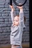 Λίγο αγόρι παιδιών στην γκρίζα sportwear ένωση tge στα γυμναστικά δαχτυλίδια ενάντια στο τουβλότοιχο στη γυμναστική Στοκ εικόνα με δικαίωμα ελεύθερης χρήσης