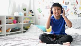 Λίγο ασιατικό αγόρι που ακούει την αγαπημένη μουσική στη συσκευή με τα ακουστικά φιλμ μικρού μήκους