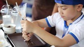 Λίγο ασιατικό αγόρι που κάνει τον ζαχαροπλάστης-μάγειρα με το χέρι συμπιέζει τη λειωμένη σοκολάτα και κάνει τα μέρη για το κέικ απόθεμα βίντεο
