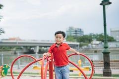 Λίγο ασιατικό αγόρι που οδηγά μια ταλάντευση και χαίρεται στοκ εικόνες