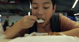 Λίγο ασιατικό αγόρι που τρώει τη σφαίρα κρέατος με το ρύζι στην τραπεζαρία καντίνων Λίγο ασιατικό παιδί που τρώει το τηγανισμένο  απόθεμα βίντεο