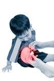 Λίγο ασιατικό αγόρι που φαίνεται πληγή το πόδι του Αθλητικοί τραυματισμός και υγεία στοκ φωτογραφίες