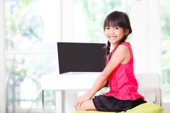 Λίγο ασιατικό κορίτσι με τον υπολογιστή Στοκ Εικόνα