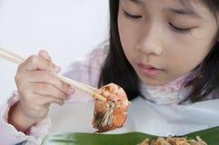 Λίγο ασιατικό κορίτσι που εξετάζει μια γαρίδα. Στοκ εικόνες με δικαίωμα ελεύθερης χρήσης