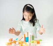 Λίγο ασιατικό κορίτσι που παίζει τους ζωηρόχρωμους ξύλινους φραγμούς Στοκ Εικόνα