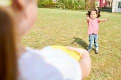 Λίγο ασιατικό κορίτσι που παίζει Frisbee στοκ εικόνες