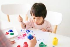 Λίγο ασιατικό κορίτσι που χρωματίζει με το πινέλο και τα ζωηρόχρωμα χρώματα στοκ εικόνα