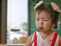 Λίγο ασιατικό κοριτσάκι απολαμβάνει το κέτσαπ ντοματών από μόνη της σε ένα εστιατόριο στοκ εικόνα