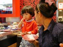 Λίγο ασιατικό κοριτσάκι που δοκιμάζει τα ακατέργαστα συστατικά, για το μαγείρεμα hotpot, που εξυπηρετεί σε μια κινούμενη ζώνη μετ στοκ φωτογραφία