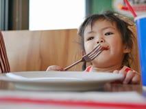 Λίγο ασιατικό κοριτσάκι που τρώει το κέτσαπ ντοματών από μόνη της σε ένα εστιατόριο στοκ εικόνες