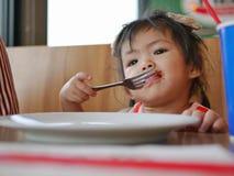 Λίγο ασιατικό κοριτσάκι που τρώει το κέτσαπ ντοματών από μόνη της σε ένα εστιατόριο στοκ φωτογραφία