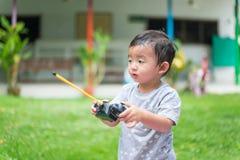 Λίγο ασιατικό παιδί που κρατά έναν ραδιο τηλεχειρισμό & x28 έλεγχος han Στοκ Φωτογραφία