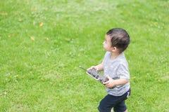 Λίγο ασιατικό παιδί που κρατά έναν ραδιο τηλεχειρισμό & x28 έλεγχος han Στοκ εικόνες με δικαίωμα ελεύθερης χρήσης
