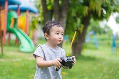 Λίγο ασιατικό παιδί που κρατά έναν ραδιο τηλεχειρισμό ελέγχοντας han Στοκ Φωτογραφία