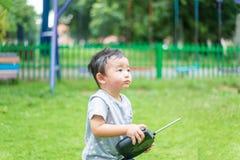 Λίγο ασιατικό παιδί που κρατά έναν ραδιο τηλεχειρισμό ελέγχοντας han Στοκ φωτογραφίες με δικαίωμα ελεύθερης χρήσης