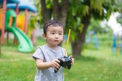 Λίγο ασιατικό παιδί που κρατά έναν ραδιο τηλεχειρισμό ελέγχοντας han Στοκ Φωτογραφίες