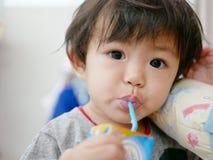 Λίγο ασιατικό πόσιμο γάλα κοριτσάκι από ένα χαρτοκιβώτιο γάλακτος από μόνη της στοκ εικόνες με δικαίωμα ελεύθερης χρήσης