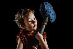 Λίγο αστείο αγόρι είναι ένα του Νεάντερταλ ή ένα cro-Magnon Αρχαίος ένας caveman με ένα τεράστιο τσεκούρι είναι απομονωμένος στο  Στοκ Εικόνες