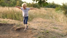 Λίγο αστείο αγόρι που παίζει στον τομέα φθινοπώρου, slowmo φιλμ μικρού μήκους