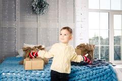 Λίγο αστείο εύθυμο αγόρι ένα παιδί κάθεται σε ένα κρεβάτι στη ημέρα των Χριστουγέννων με τα κιβώτια δώρων στο άσπρο πλεκτό μαλλί  Στοκ Εικόνα