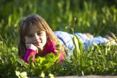 Λίγο αστείο κορίτσι που βρίσκεται στην πράσινη χλόη Ευτυχία Στοκ φωτογραφία με δικαίωμα ελεύθερης χρήσης