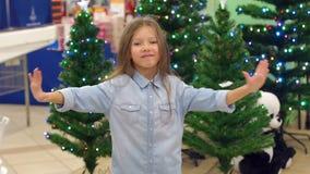 Λίγο αστείο κορίτσι στην υπεραγορά χορεύει στο υπόβαθρο των χριστουγεννιάτικων δέντρων απόθεμα βίντεο
