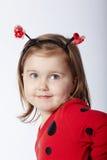 Λίγο αστείο κορίτσι στο κοστούμι ladybug Στοκ Εικόνες