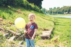 Λίγο αστείο παιχνίδι αγοριών με το κίτρινο μπαλόνι υπαίθριο Στοκ Εικόνες