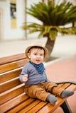 Λίγο λατρευτό αγοράκι σε ένα καπέλο αχύρου και ένα καφετί κάθισμα εσωρούχων Στοκ εικόνα με δικαίωμα ελεύθερης χρήσης
