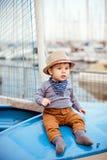 Λίγο λατρευτό αγοράκι σε ένα καπέλο αχύρου και ένα καφετί κάθισμα εσωρούχων Στοκ εικόνες με δικαίωμα ελεύθερης χρήσης
