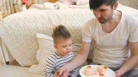 Λίγο λατρευτό αγόρι που γιορτάζει τα γενέθλιά του με το νέο πατέρα τρώει το κέικ στην κρεβατοκάμαρα φιλμ μικρού μήκους