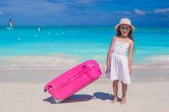 Λίγο λατρευτό κορίτσι με τη μεγάλη ζωηρόχρωμη βαλίτσα στα χέρια στην άσπρη εξωτική παραλία Στοκ Φωτογραφία