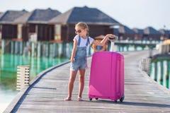 Λίγο λατρευτό κορίτσι με τις μεγάλες αποσκευές σε ξύλινο Στοκ Φωτογραφία