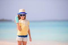 Λίγο λατρευτό κορίτσι με το suntan μπουκάλι λοσιόν στην παραλία Στοκ Εικόνα
