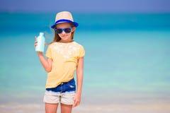 Λίγο λατρευτό κορίτσι με το suntan μπουκάλι λοσιόν στην παραλία Στοκ Φωτογραφία