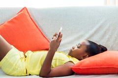 Λίγο αφρικανικό κορίτσι που βάζει στον καναπέ με την ταμπλέτα Στοκ φωτογραφία με δικαίωμα ελεύθερης χρήσης