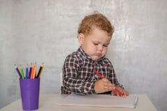 Λίγο ευρωπαϊκό αγόρι σύρει με τα χρωματισμένα μολύβια στοκ φωτογραφίες
