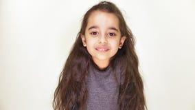 Λίγο ευτυχές κορίτσι που χαμογελά και που εξετάζει τη κάμερα, πορτρέτο, άσπρο υπόβαθρο 50 fps φιλμ μικρού μήκους