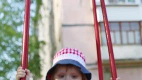 Λίγο ευτυχές κορίτσι στην ταλάντευση καπέλων και φορεμάτων στην παιδική χαρά παιδιών απόθεμα βίντεο