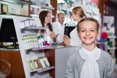 Λίγο ευτυχές κορίτσι στο φαρμακείο με τους γονείς και το φαρμακοποιό στοκ εικόνα με δικαίωμα ελεύθερης χρήσης