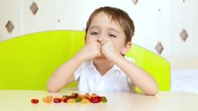 Λίγο ευτυχές παιδί κάθεται στον πίνακα και εξετάζει τις φωτεινές καραμέλες φρούτων Το αγόρι παίρνει την καραμέλα και την τρώει φιλμ μικρού μήκους
